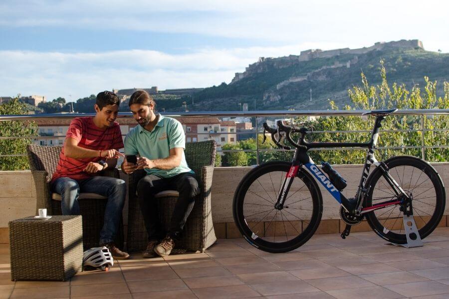 Dos personas toman café sentadas mientras examinan un teléfono móvil con una bicicleta Giant al lado